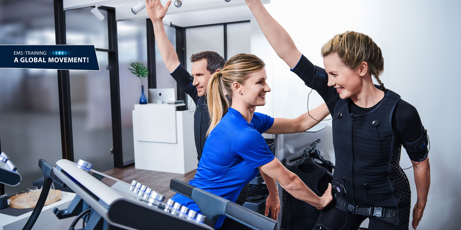 personal trainer exercises two people on miha bodytec 2 machines