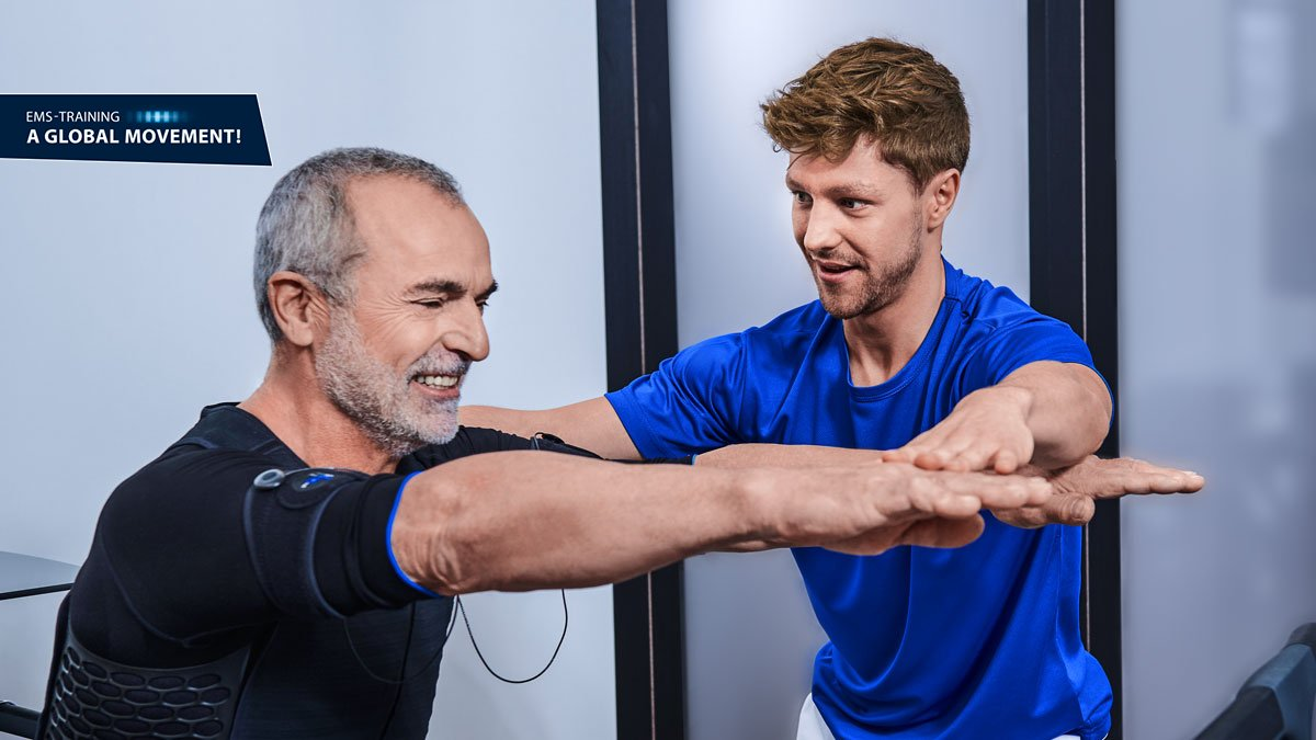 personal trainer exercises man in training pose