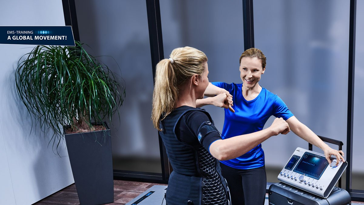 woman trains with personal trainer at a mobile miha bodytec 2 station