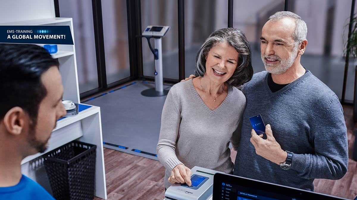 couple puts their miha bodytec training card on the reader